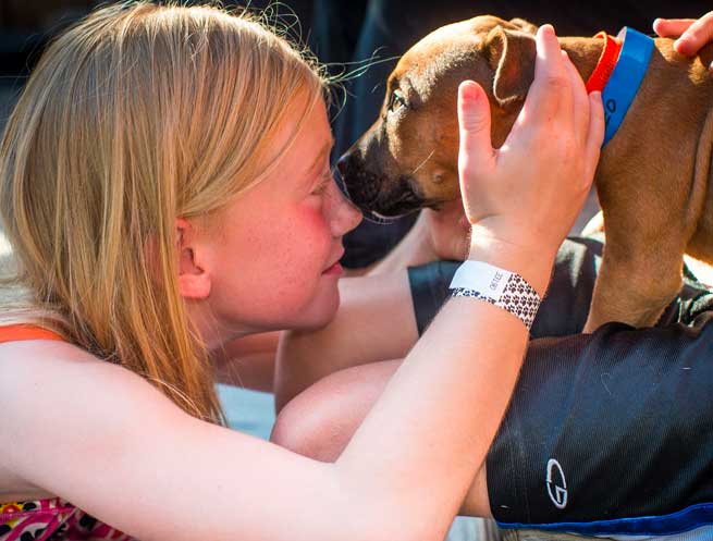 Little girl with puppy adopted from Operation Kindness at an adoption event | North Texas' Leading No-Kill Animal Shelter